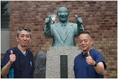 日本指圧専門学校事務長の浪越雄二氏(写真左)と小野田茂氏(写真右)。同校前の浪越徳治郎氏の銅像前にて